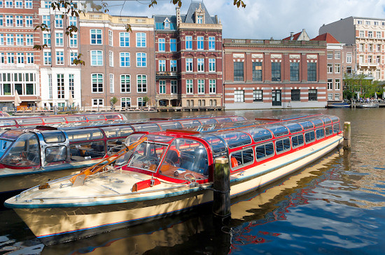 Sightseeing boat waiting for tourist on Amsterdam canal.
