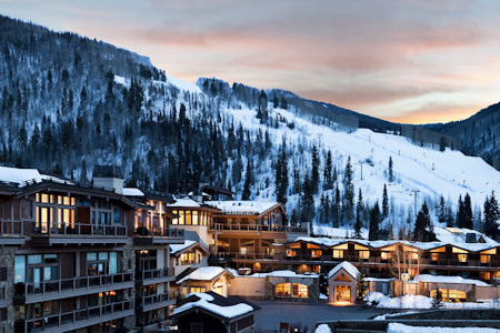 Winter view of the Manor Vail Lodge with ski runs in background.