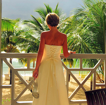 Bride looks out over water and beach.