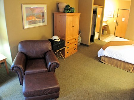 Comfortable arm chair, second HDTV is in cabinet.
