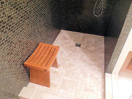 Seat inside shower stall.
