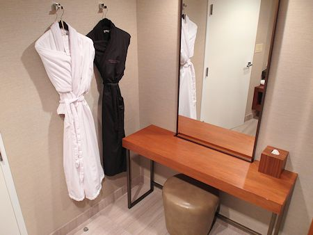 Plush robes and a makeup table in the standard room.
