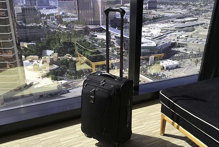 "Travelpro Crew 11 21"" Expandable Spinner Carry-On overlooking the Las Vegas Strip."